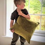 Child holding a velvet cushion with a bespoke engraving of child's artwork